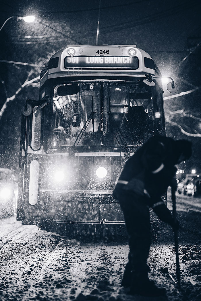worker clearing snow for tram